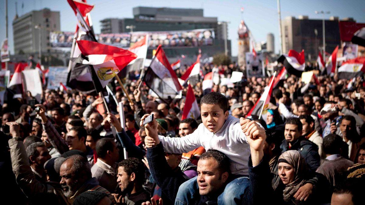 Auf einem Platz in Ägypten protestiert eine große Anzahl von Menschen. Kinder und Erwachsene sind darunter.