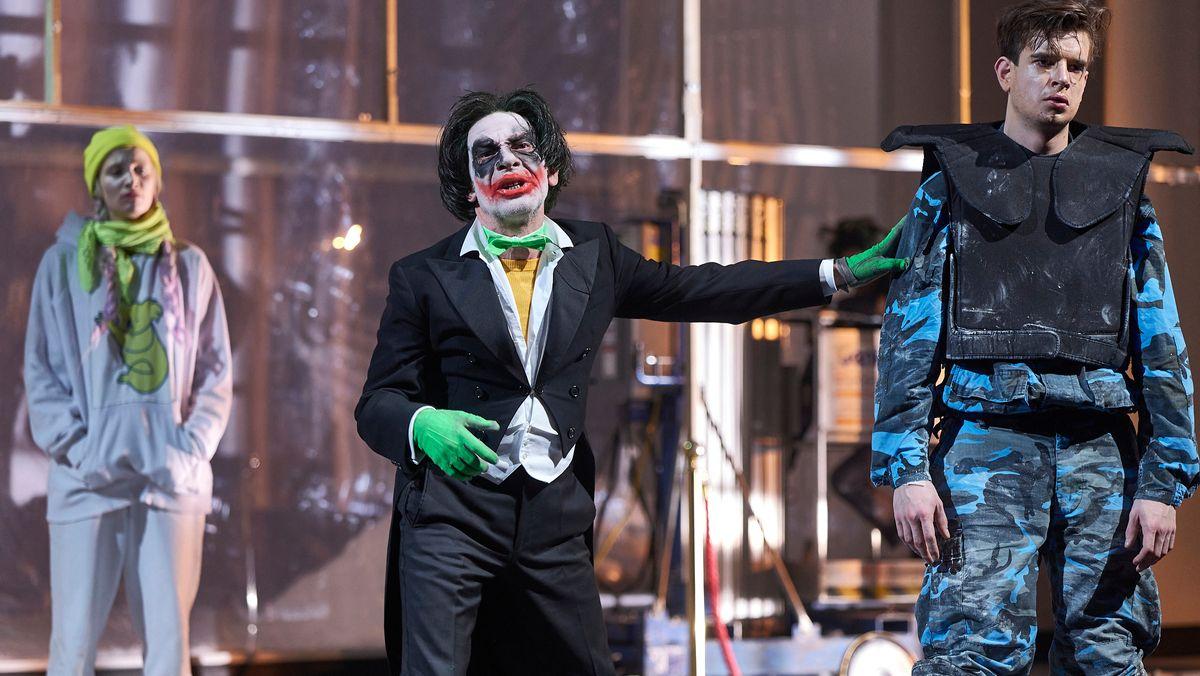 """Drei Schauspieler auf der Bühne in Elfriede Jelineks """"Schwarzwasser"""" in Wien, der mittlere mit Gesicht in Clowns-Schminke"""