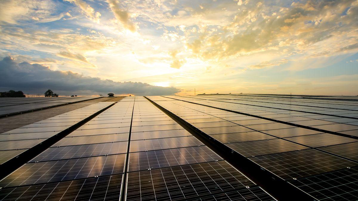Ein Feld mit großen Solarpanels. Im Hintergrund strahlt die Sonne durch den bewölkten Himmel.