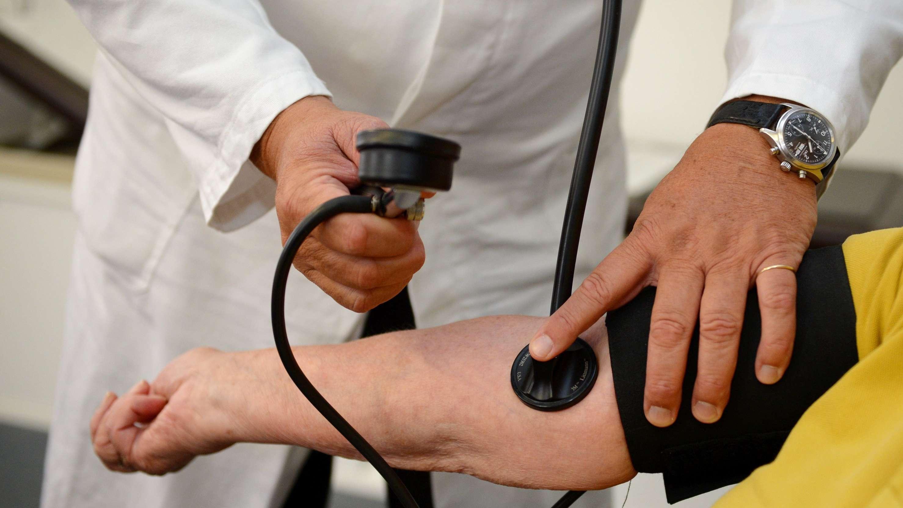 Ein Arzt misst einer Patientin den Blutdruck