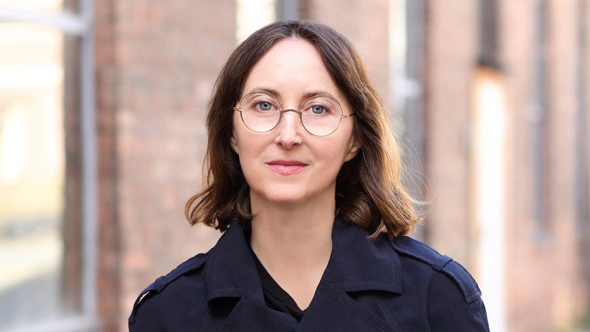 Die Künstlerin Maria Eichhorn steht vor einem Haus