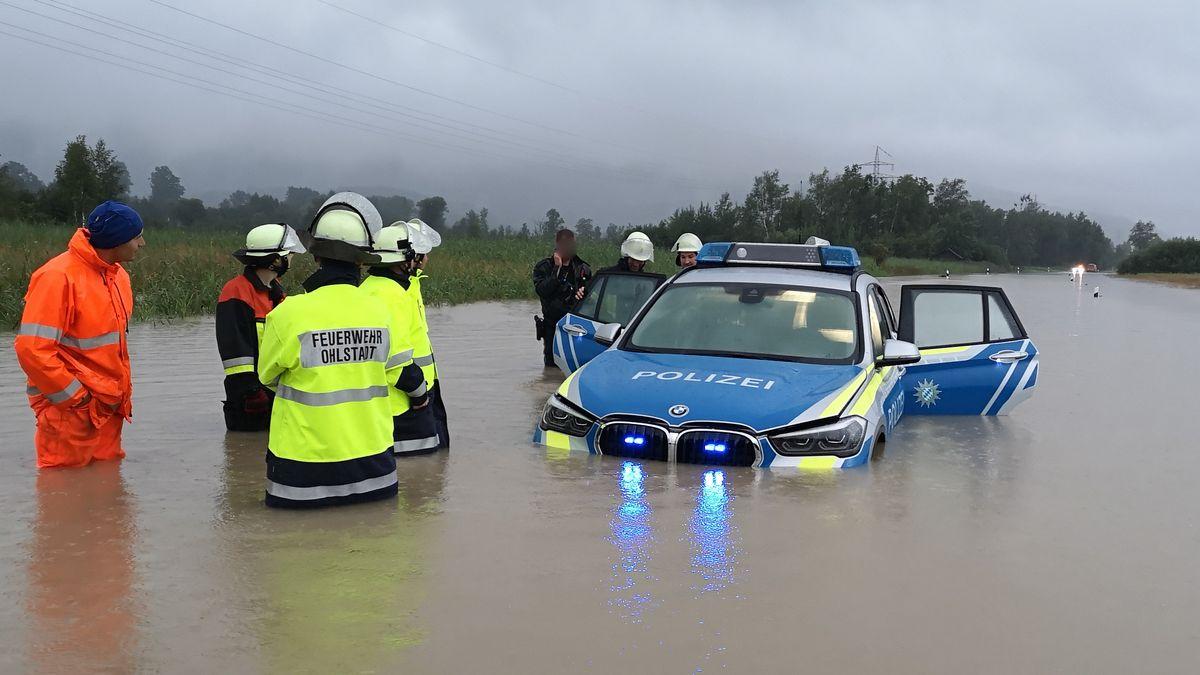Ein Polizeiauto steht mit geöffneten Türen auf der B2 zwischen Murnau und Ohlstadt. Das Wasser reicht bis kapp unter die Motorhaube. Um das Auto herum stehen Polizisten und Feuerwehrmänner.