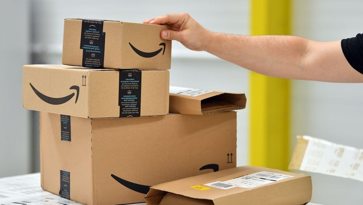 Ein Mitarbeiter stapelt Packe mit dem Logo des Versandhändlers Amazon.