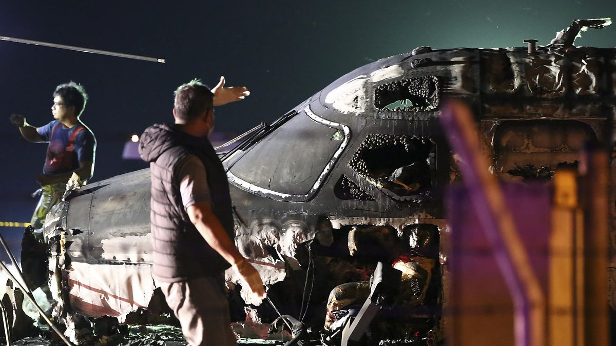 Flughafenmitarbeiter stehen neben den Überresten eines ausgebrannten Flugzeugs am Flughafen Manila.