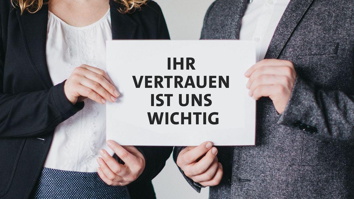 """Ein Mann und eine Frau halten gemeinsam ein Schild in der Hand: """"Ihr Vertrauen ist uns wichtig"""""""