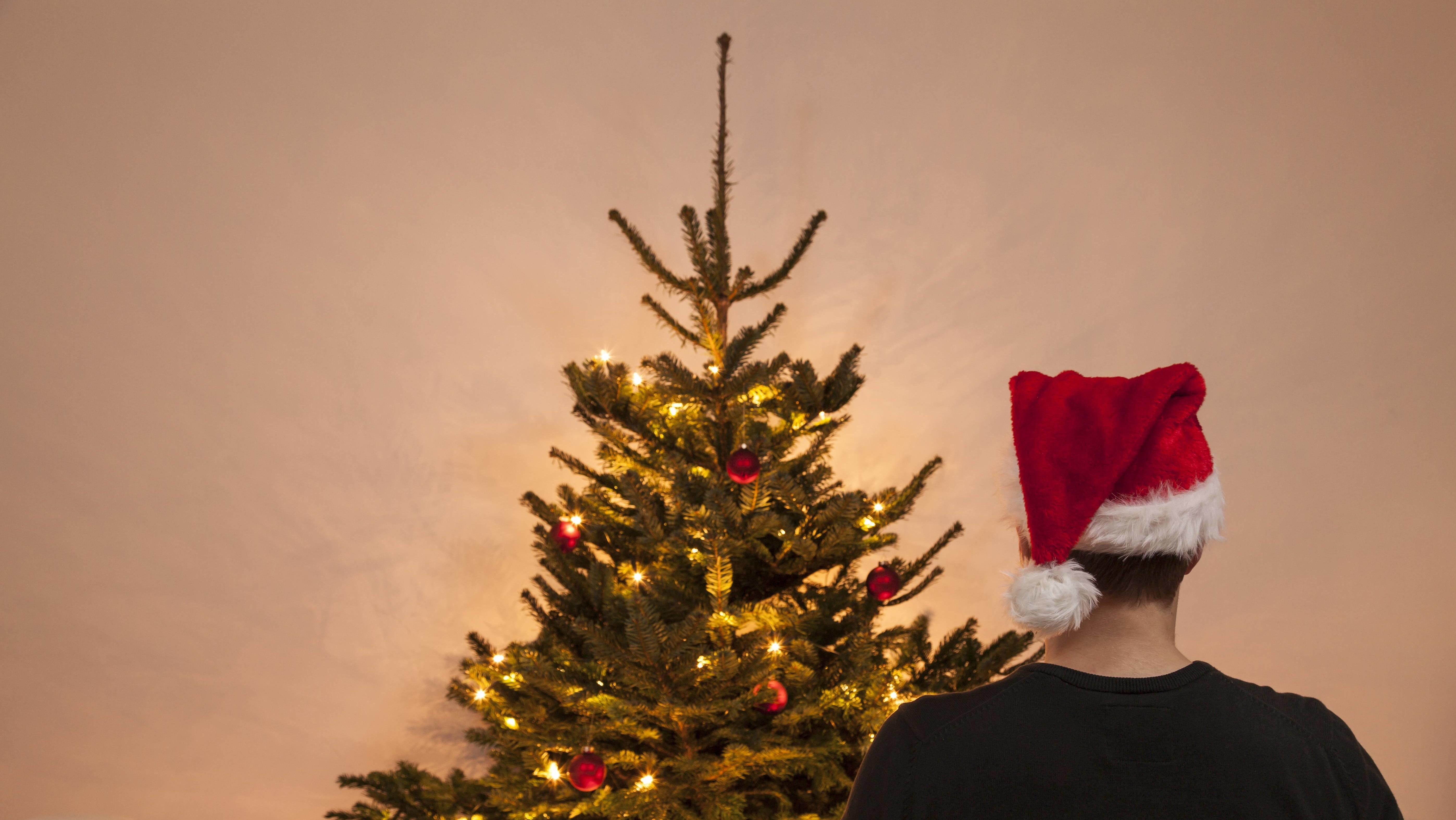 Mann alleine vorm Weihnachtsbaum