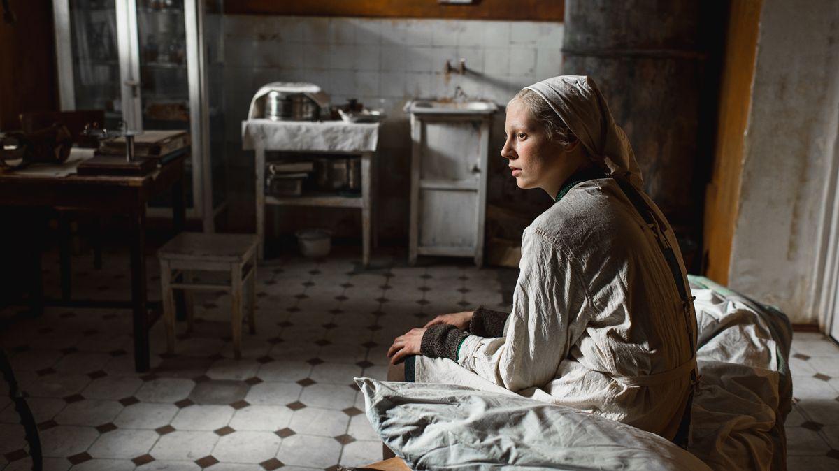 """Junge Frau sitzt in einer Nachkriegs-Küche (Filmszene aus """"Bohnenstange"""")"""