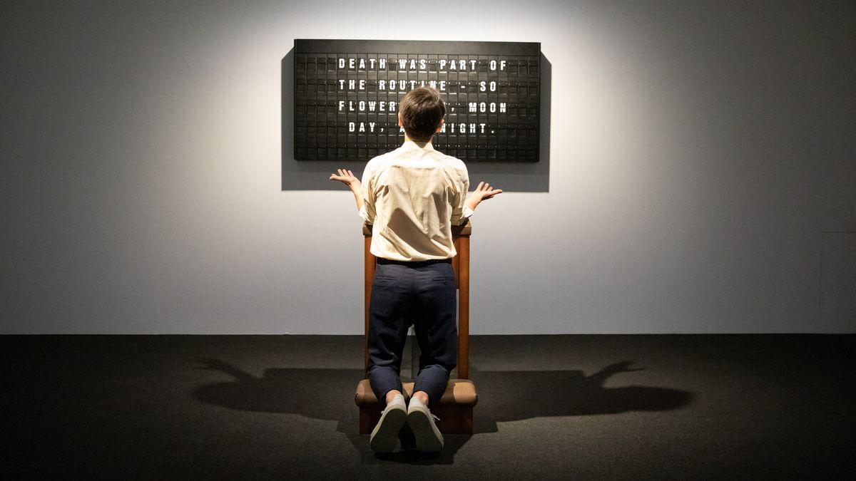 Ein junger Mann kniet mit dem Rücken zum Betrachter auf einem Betpult, vor ihm zeigt eine Anzeigetafel ein Bonmot