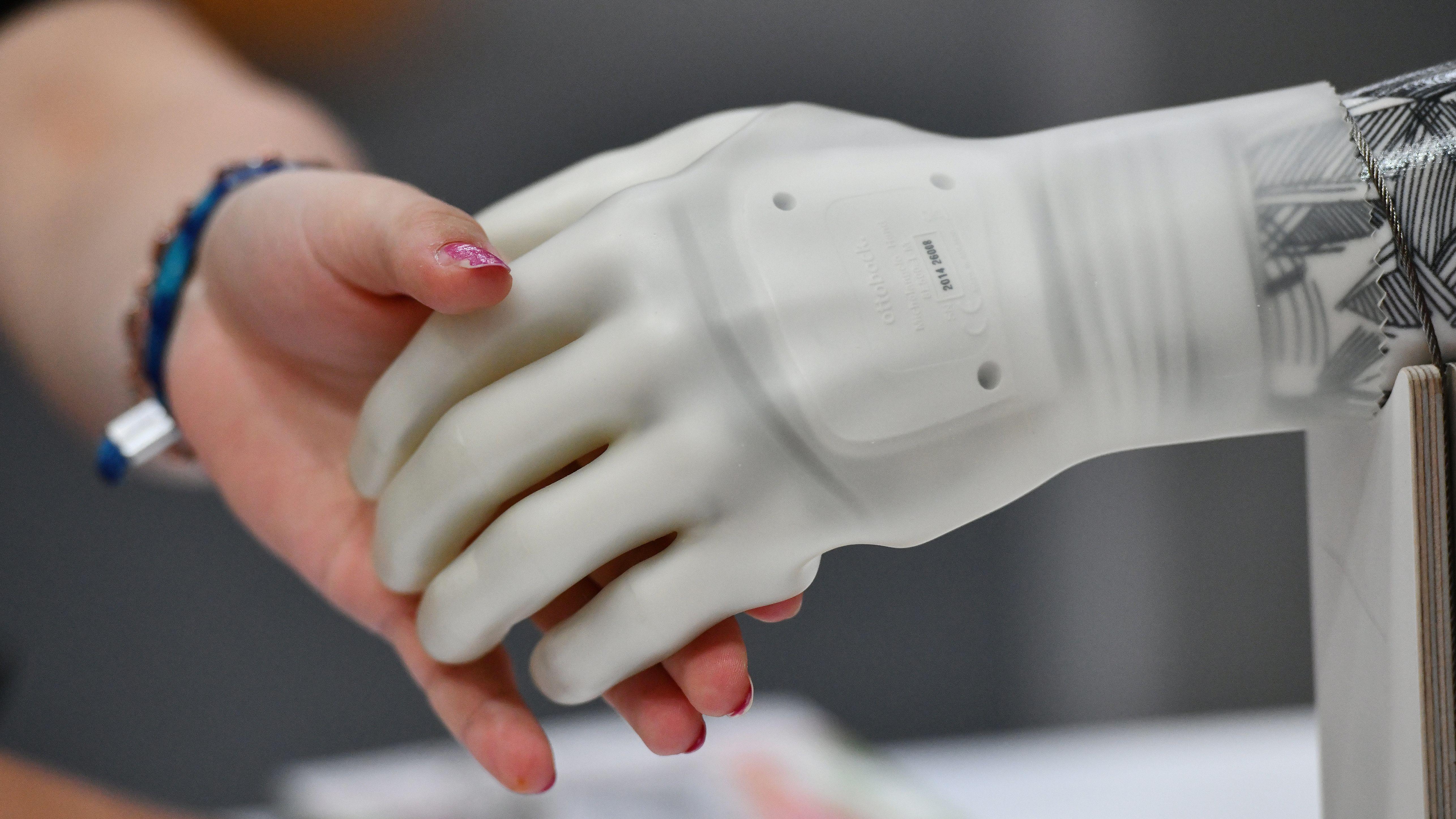 Eine Hand greift nach der künstlichen Hand eines Roboters