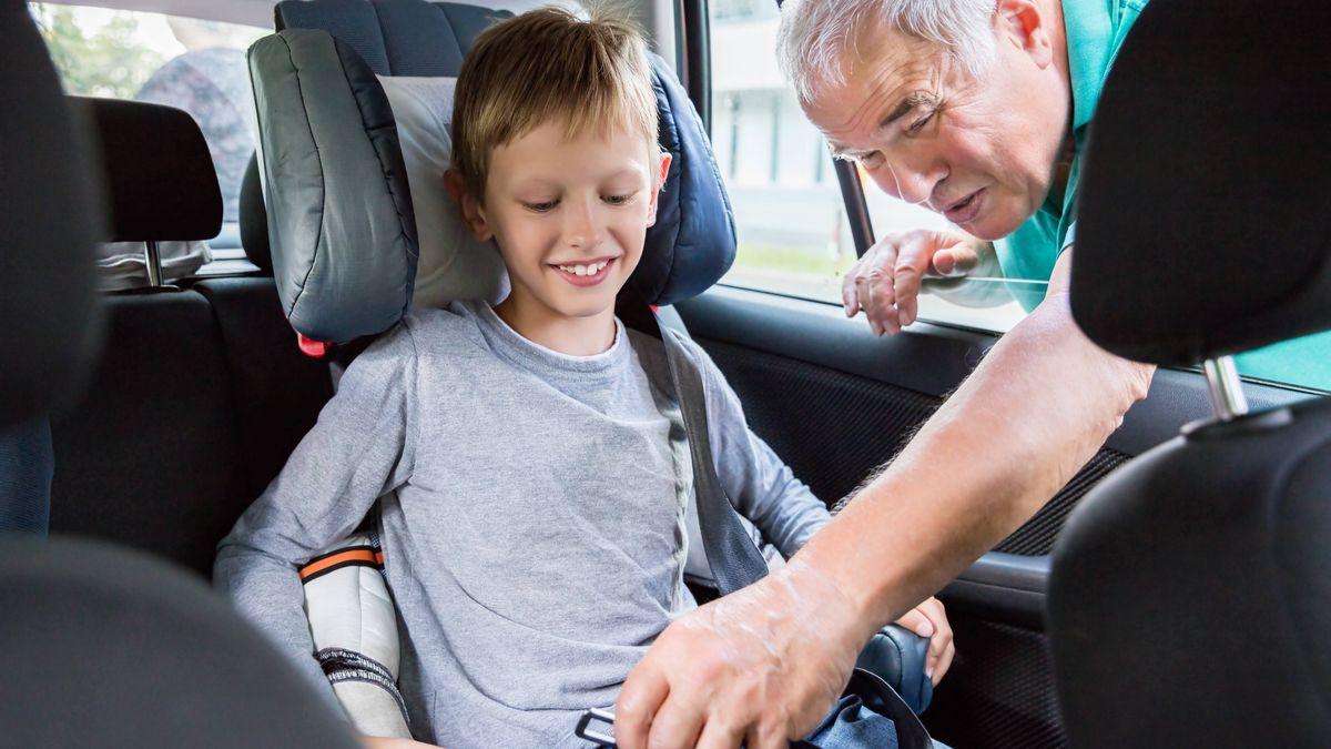 Großvater legt dem Enkel den Sicherheitsgurt an