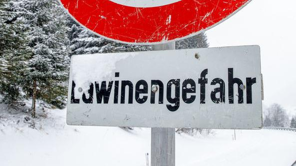 """""""Lawinengefahr"""" steht auf einem Schild in verschneiter Gebirgslandschaft in Österreich - Symbolbild"""