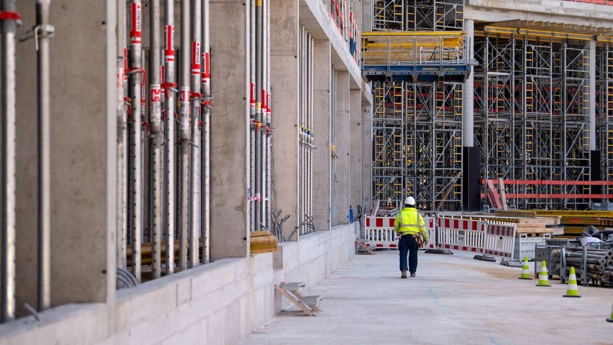 Ein Bauarbeiter geht über eine große Baustelle (Symbolbild)