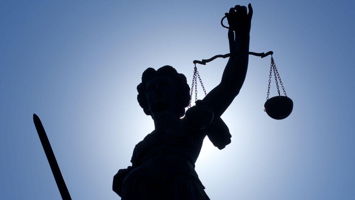 Justitia hält eine Waage und ein Schwert in den Händen