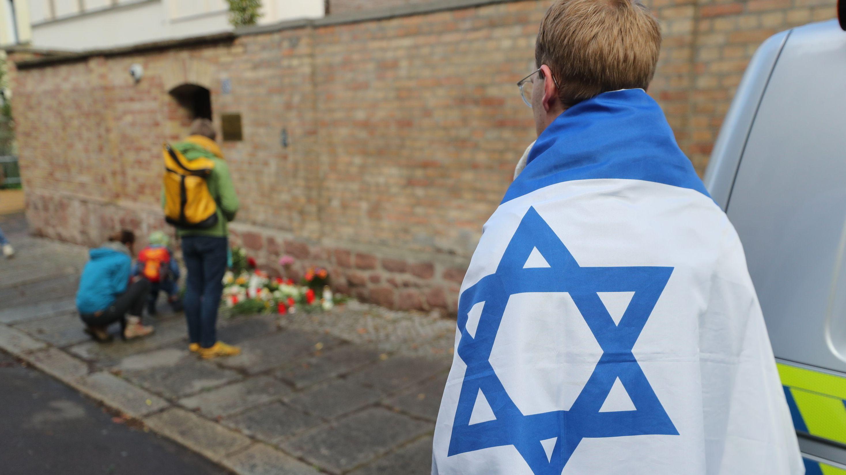 10.10.2019, Sachsen-Anhalt, Halle: Ein Mann mit einer Israel-Flagge vor der Synagoge. Bei Angriffen mitten in Halle an der Saale in Sachsen-Anhalt sind gestern vor einer Synagoge und in einem Döner-Imbiss zwei Menschen erschossen worden.