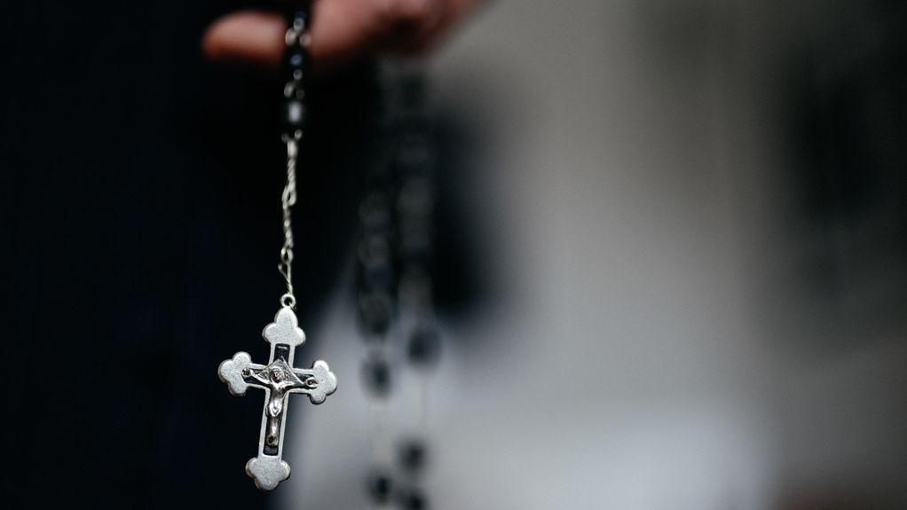 Ein Zinnkreuz baumelt an einem Rosenkranz vor unscharfem Hintergrund