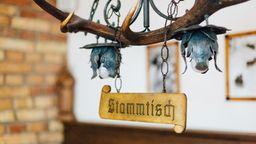 """Eine Lampe mit einem """"Stammtisch""""-Schild darunter.   Bild:BR/Sylvia Bentele"""