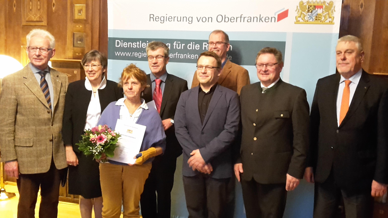 Preisträger des Integrationspreises stehen vor einer Leinwand der Regierung von Oberfranken
