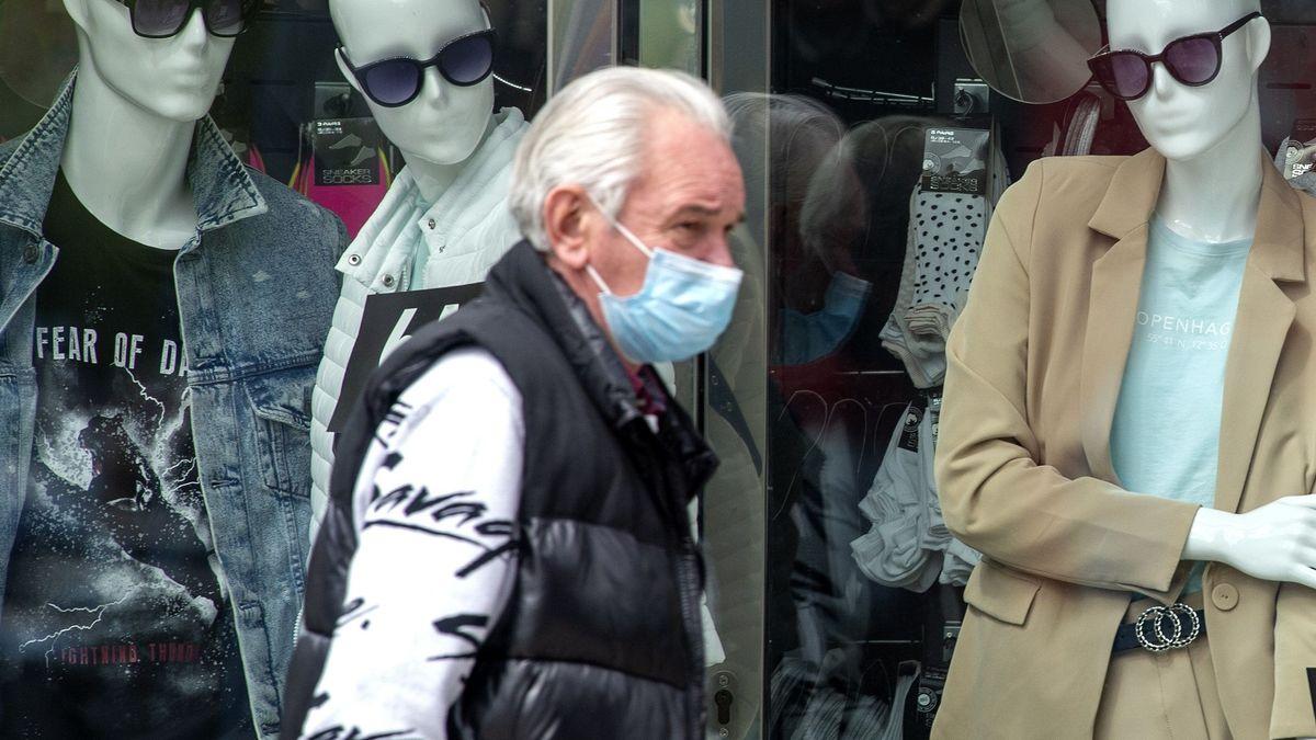 Ein Mann mit einer Schutzmaske geht an einem Modeladen vorbei.