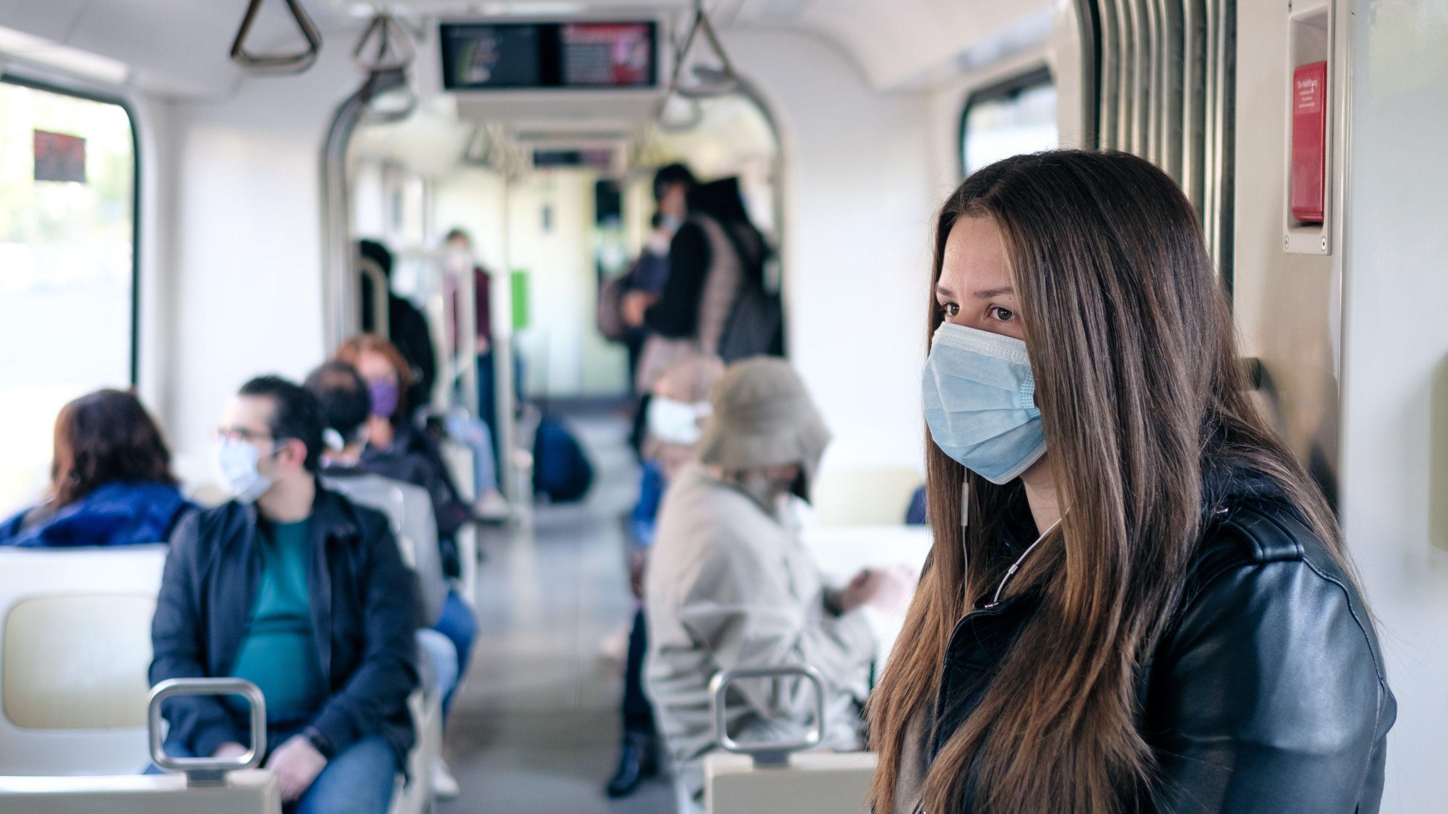 Unterwegs im Öffentlichen Nahverkehr: eine Frau mit Mund-Nasen-Schutzmaske
