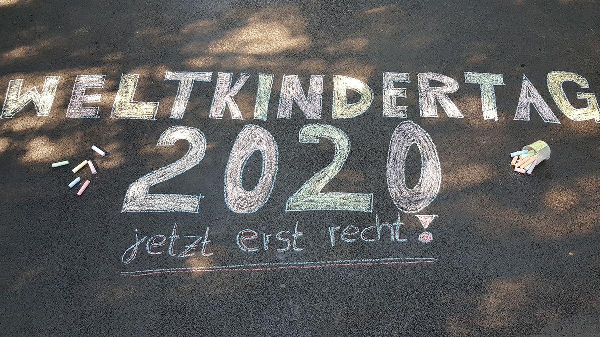 Mit weißer Kreide wurde auf eine Straße folgender Satz gemalt: Weltkindertag, 2020, jetzt erst recht!