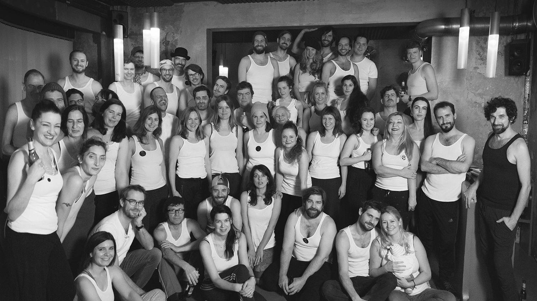 Die Mitglieder des Münchner Kneipenchors auf einem schwarz-weißen Gruppenfoto, in Unterhemden und Jogginhosen