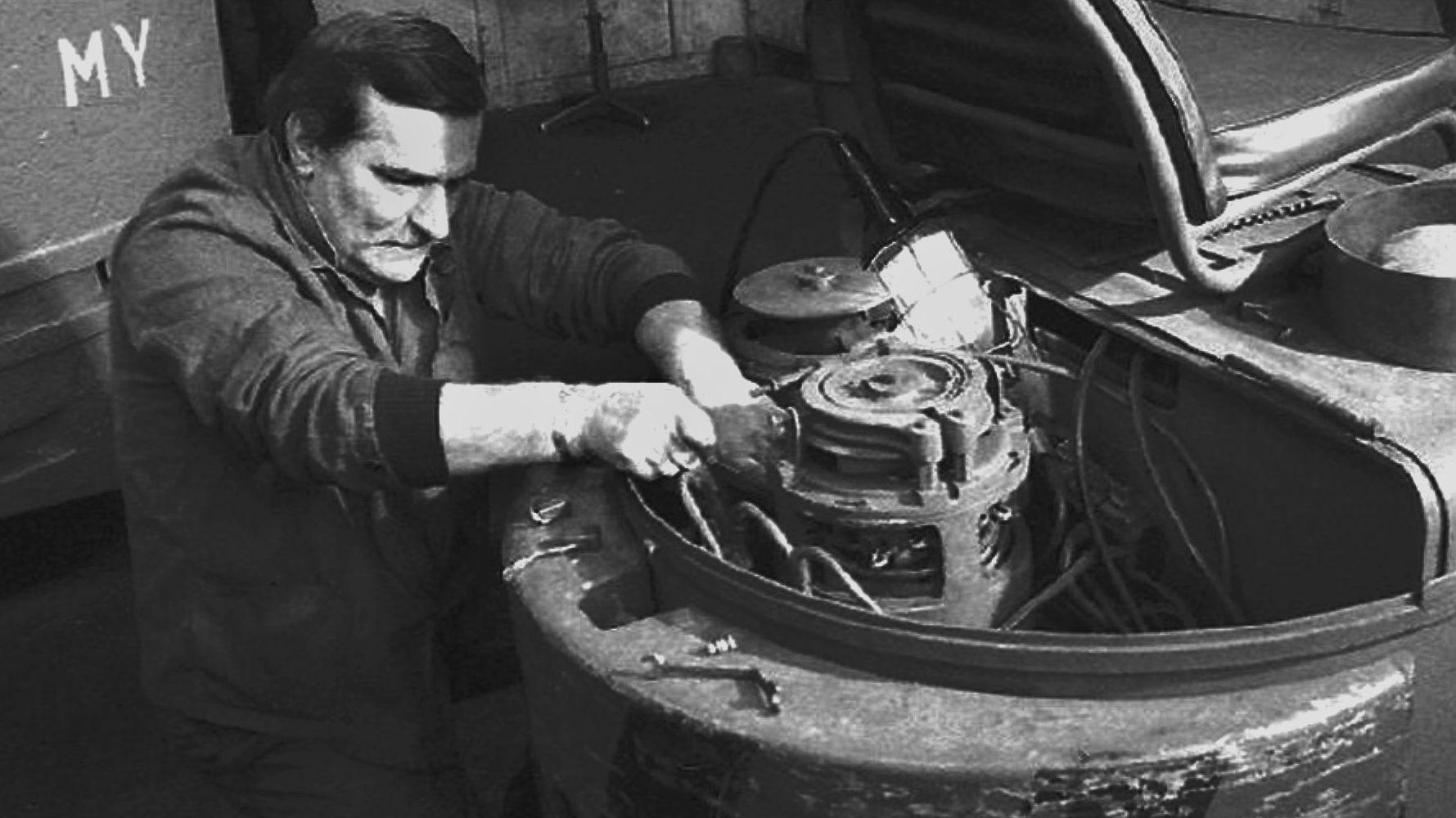 """Lech Wałęsa als Elektriker bei der Arbeit in der Danziger Werft """"Lenin"""" (Schwarz-Weiß-Aufnahme von 1989)"""