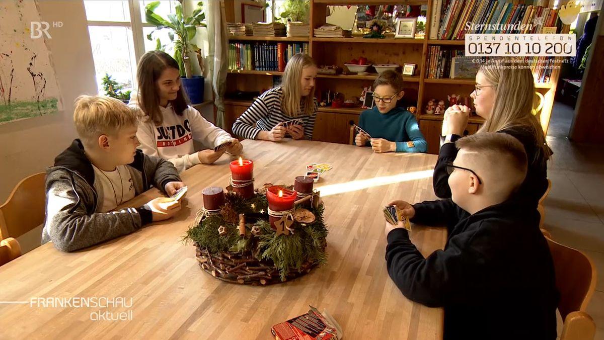 Kinder sitzen an einem Tisch, auf dem ein Adventskranz steht.