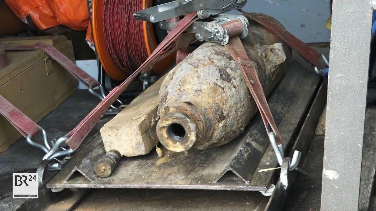 Eine stark verwitterte Fliegerbombe liegt auf einer Metalltrage, befestigt mit einem roten Spanngurt.