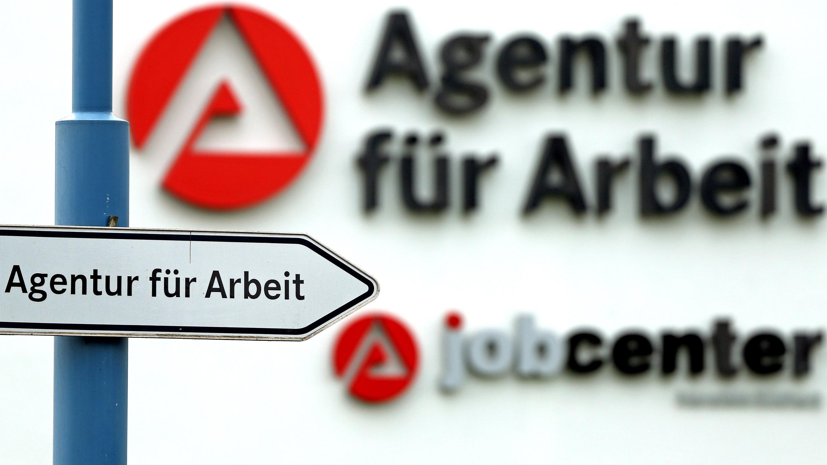 Ein Schild weist den Weg zur Agentur für Arbeit.