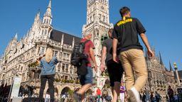 Passanten gehen über den Marienplatz im Herzen der bayerischen Landeshauptstadt am Rathaus vorbei. Zur Eindämmung des Coronavirus hat die Stadt München eine Maskenpflicht auf bestimmten öffentlichen Plätzen und Straßen der Innenstadt erlassen . | Bild:dpa/ Peter Kneffel