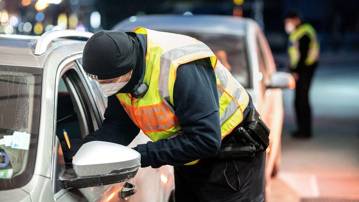Polizist bei Kontrolle eines Autofahrers bei der Einreise in Kiefersfelden