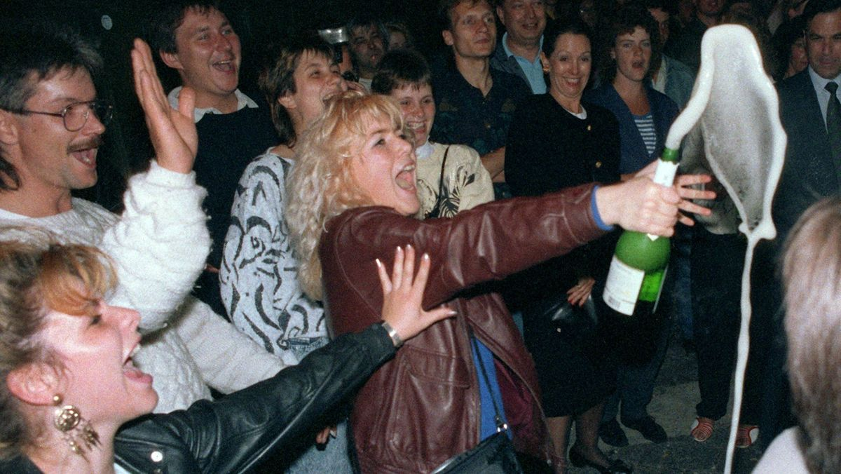 Feiernde Menschen mit Sektflasche am Berliner Alexanderplatz zur Einführung der D-Mark am 1. Juli 1990