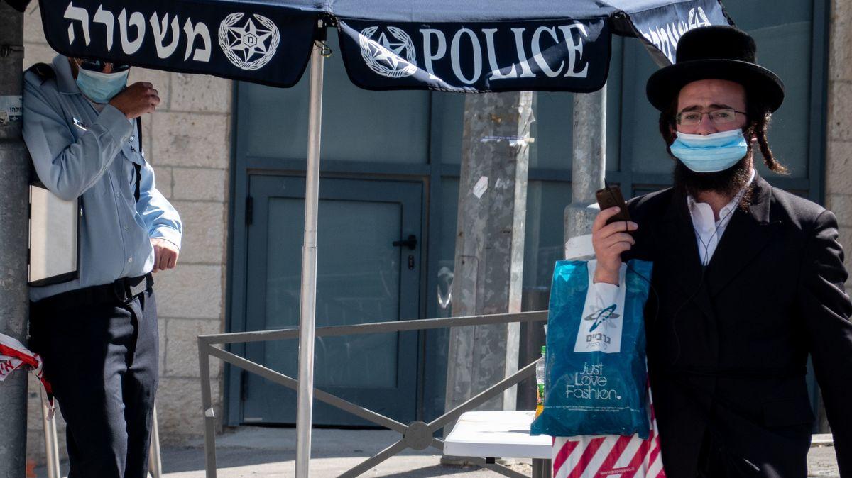 Ein orthodoxer Jude geht mit Mundschutz über eine Straße.