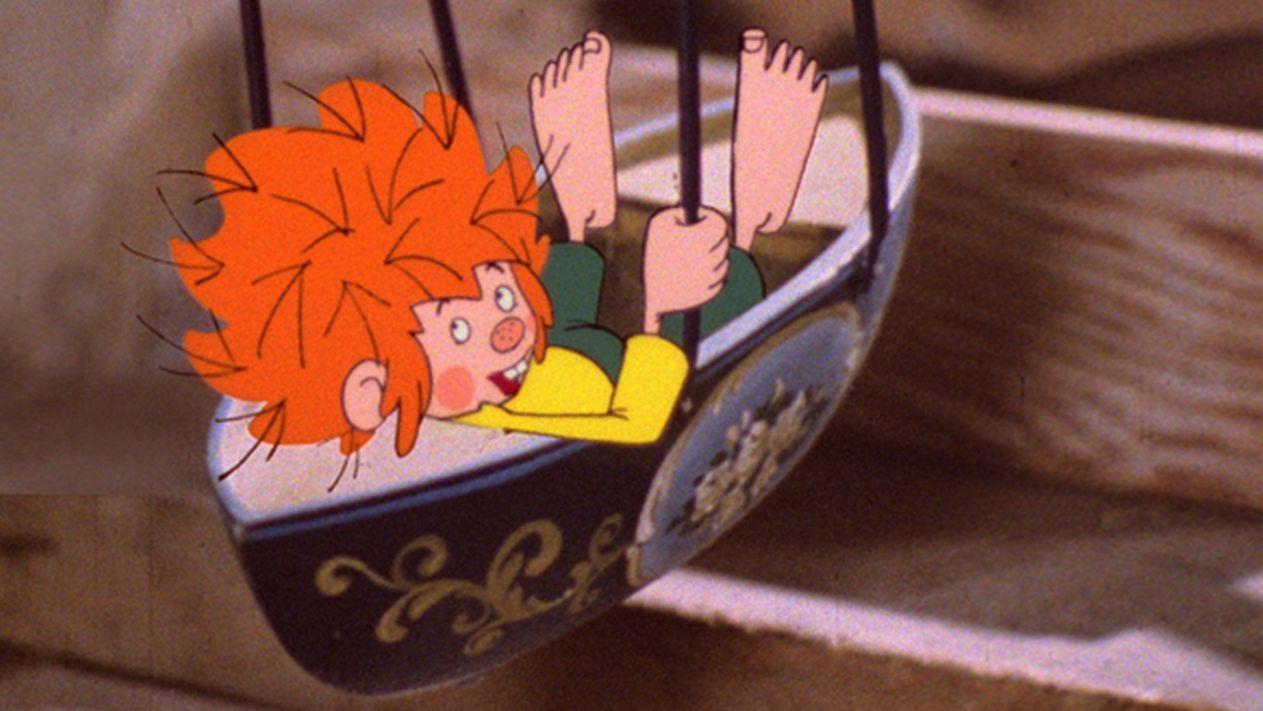 Pumuckl balanciert in seiner Schiffschaukel und blickt keck über die Schulter
