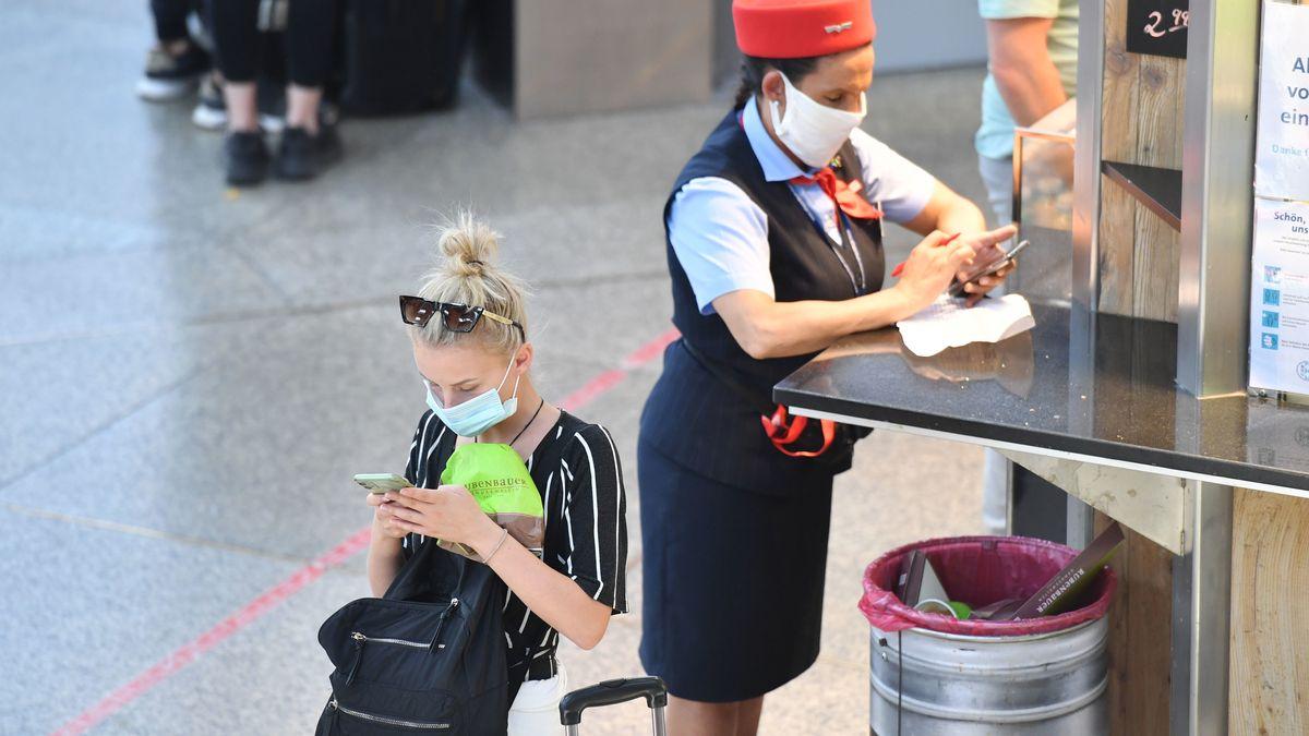 Reisende und Mitarbeiterin der DB am Hauptbahnhof München