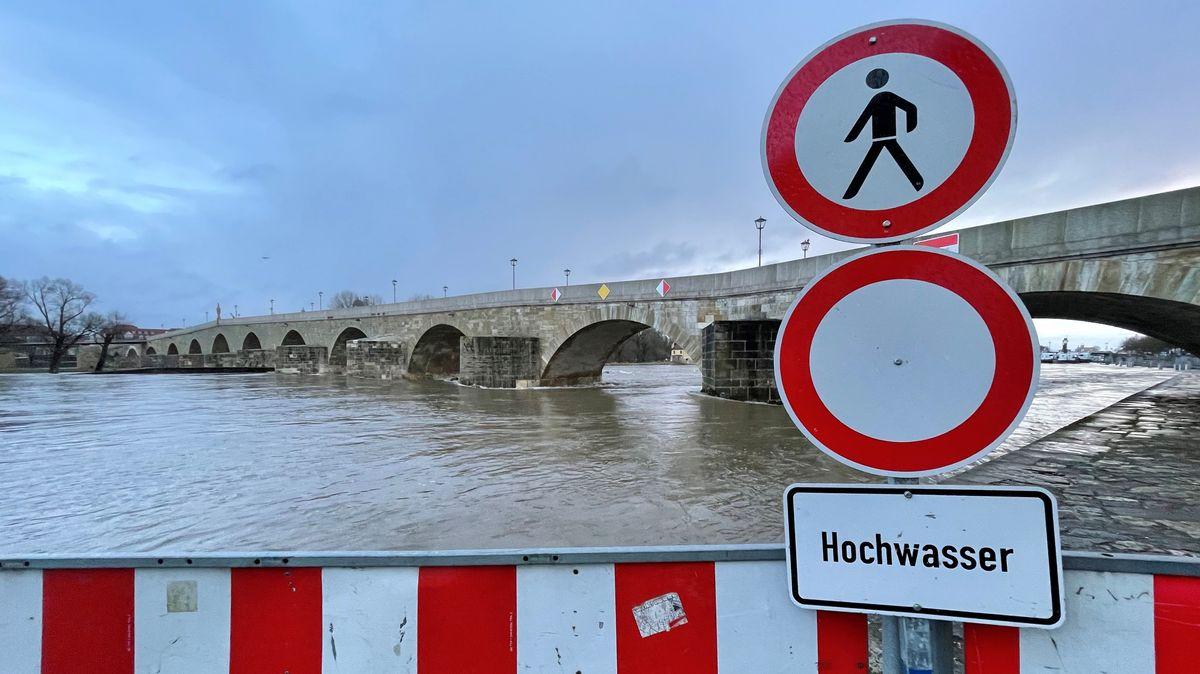 Am Donauufer an der Steinernen Brücke in Regensburg steht ein Hochwasser-Hinweisschild.