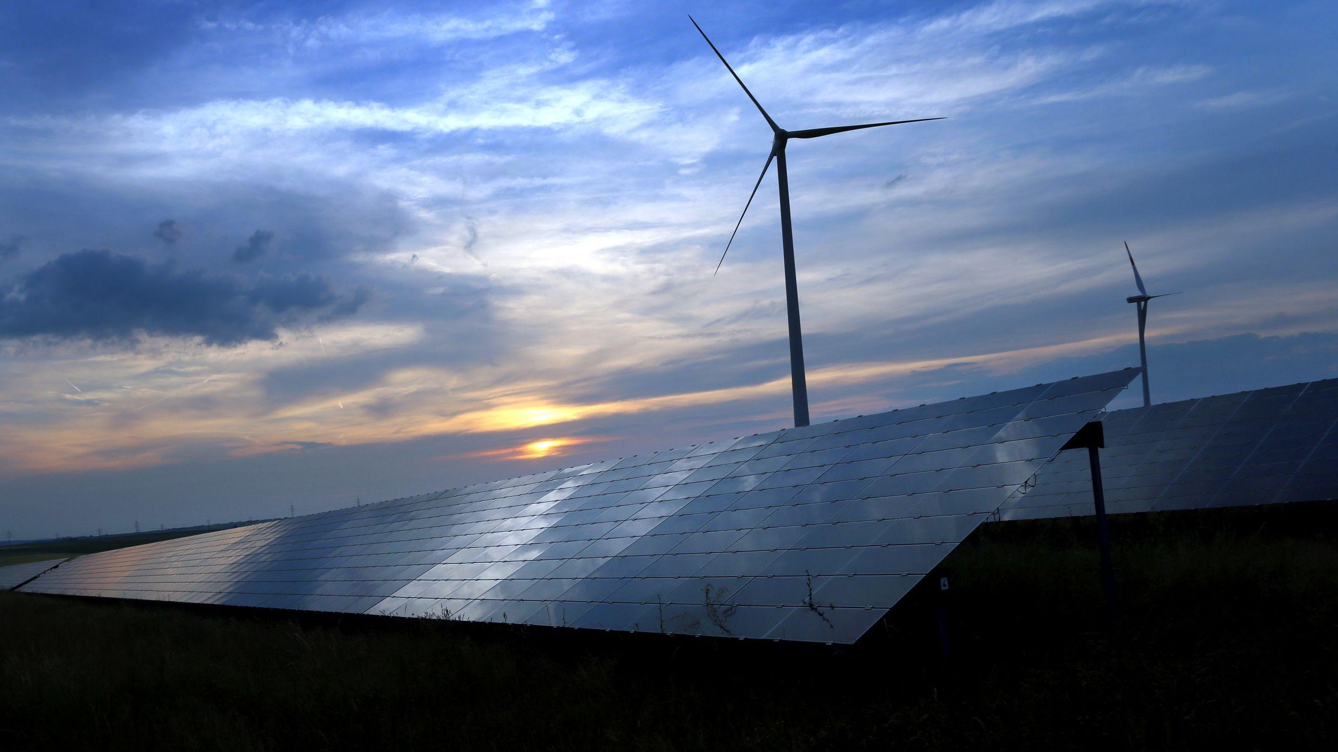 Kitzingen: Der mit Wolken überzogene Abendhimmel spiegelt sich auf den Solarzellen einer vor Windrädern stehenden Solarkraftanlage.