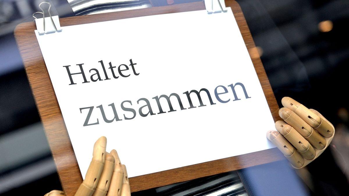 """Ein Schild mit der Aufschrift """"Haltet zusammen"""" liegt in den Händen einer Schaufensterfigur in einem geschlossenen Geschäft."""