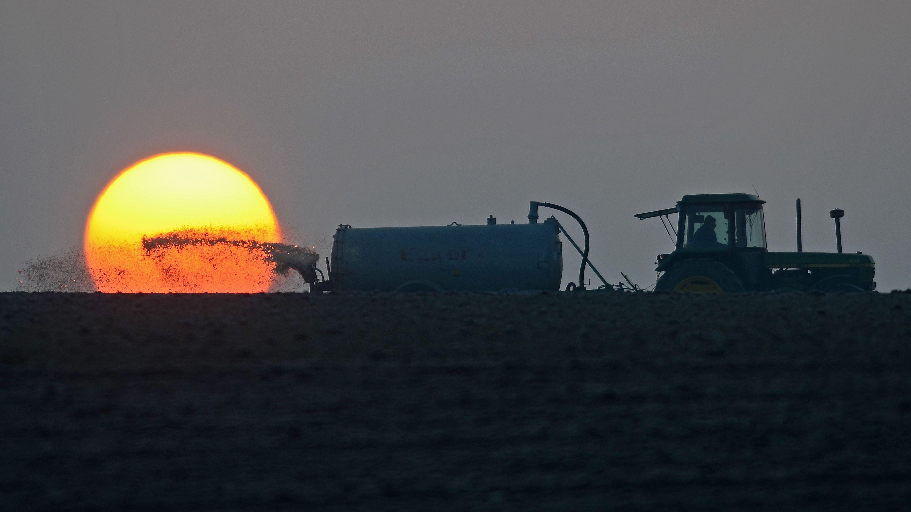 Traktor bringt vor Sonnenuntergang Gülle aufs Feld