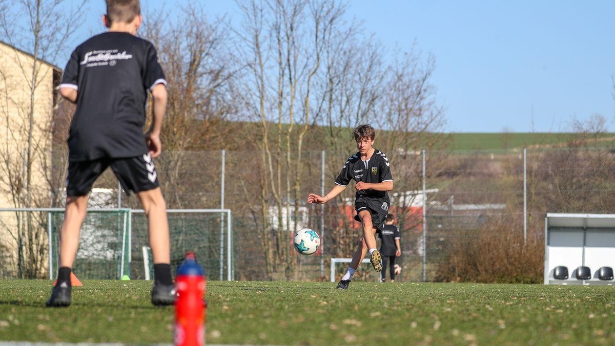 Zwei Jugendliche spielen sich einen Fußball zu.