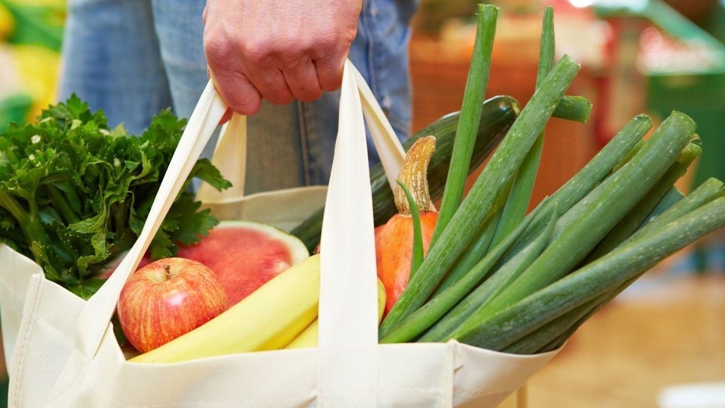 Eine weiße Einkaufstasche aus Stoff mit Äpfeln, Bananen und weiteren Obst- und Gemüsesorten