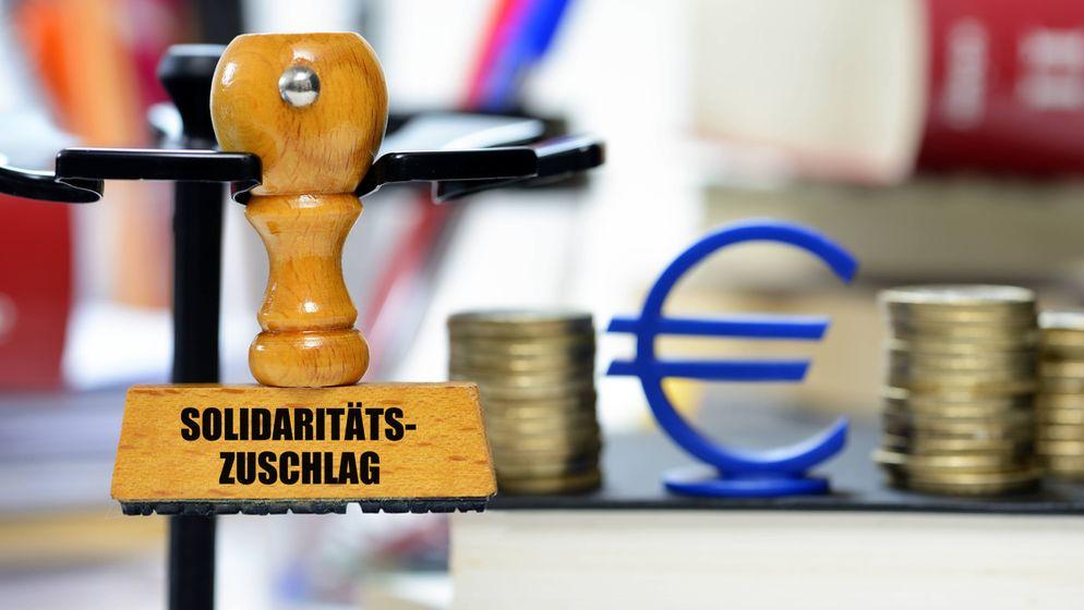 Stempel mit der Aufschrift Solidaritätszuschlag (Symbolbild)   Bild:picture alliance/chromorange/Christian Ohde