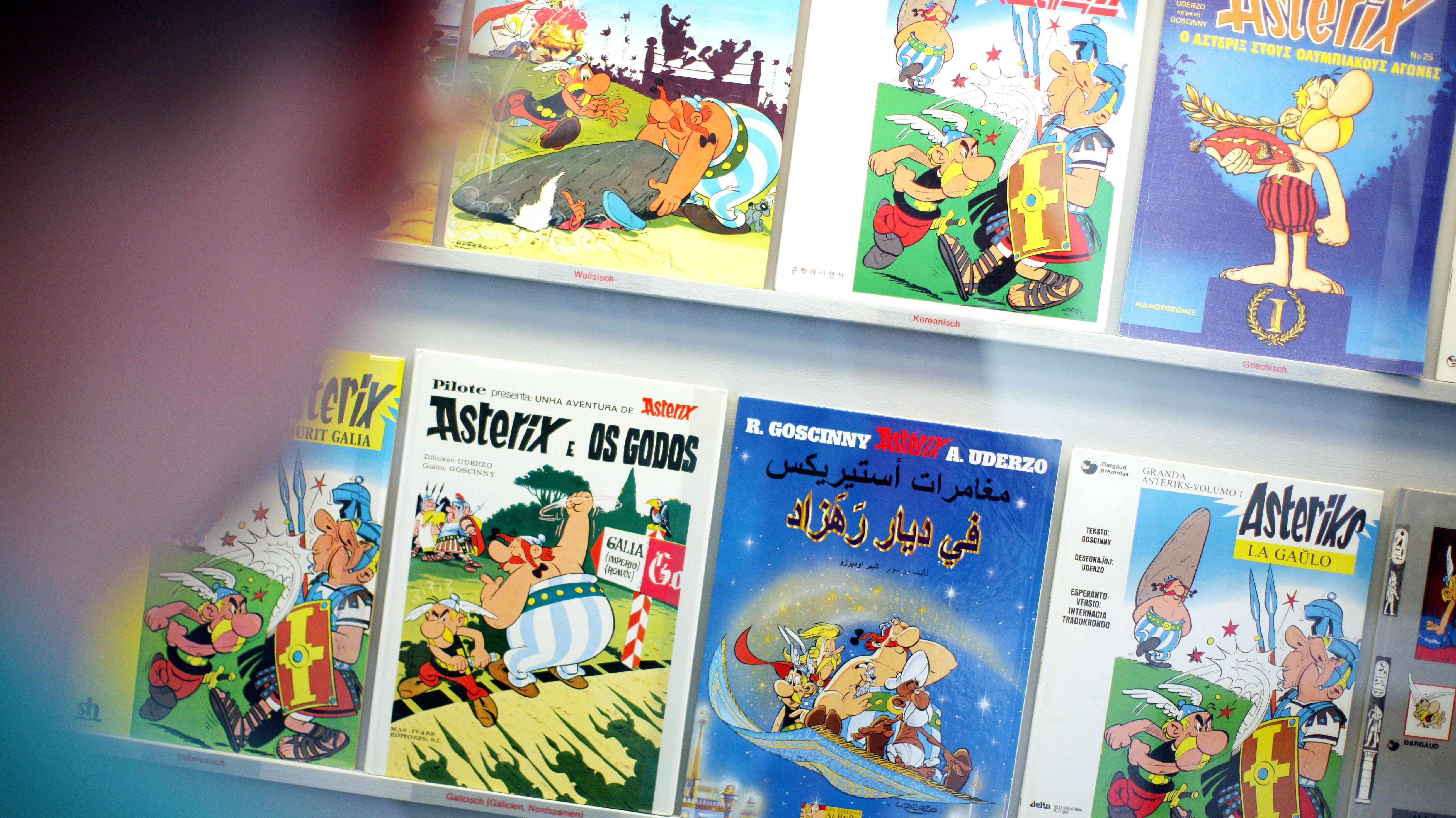 Ein Mensch steht vor einem Regal, in dem Asterix-Comics in verschiedenen Sprachen stehen.