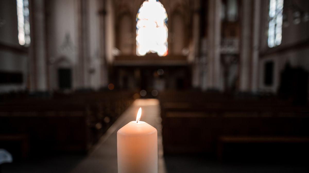 Eine Kerze brennt in einer Kirche
