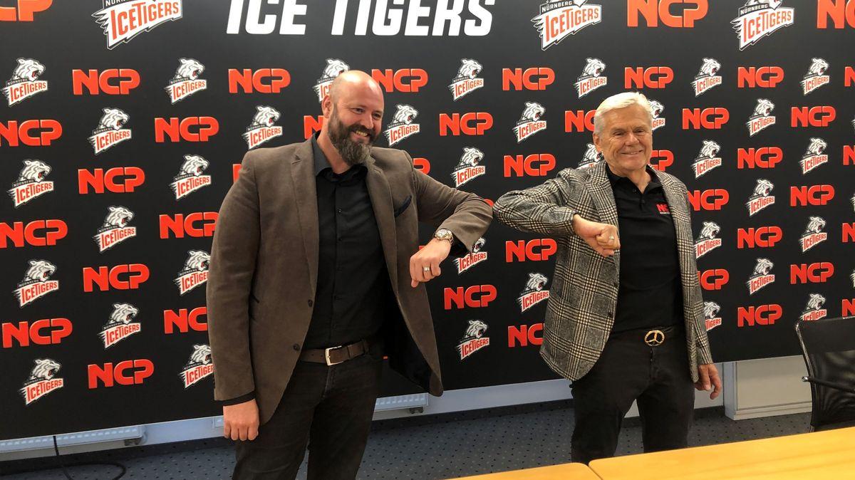 Zwei Männer posieren vor Ice Tigers Sponsorenwand und berühren sich mit den Ellbogen