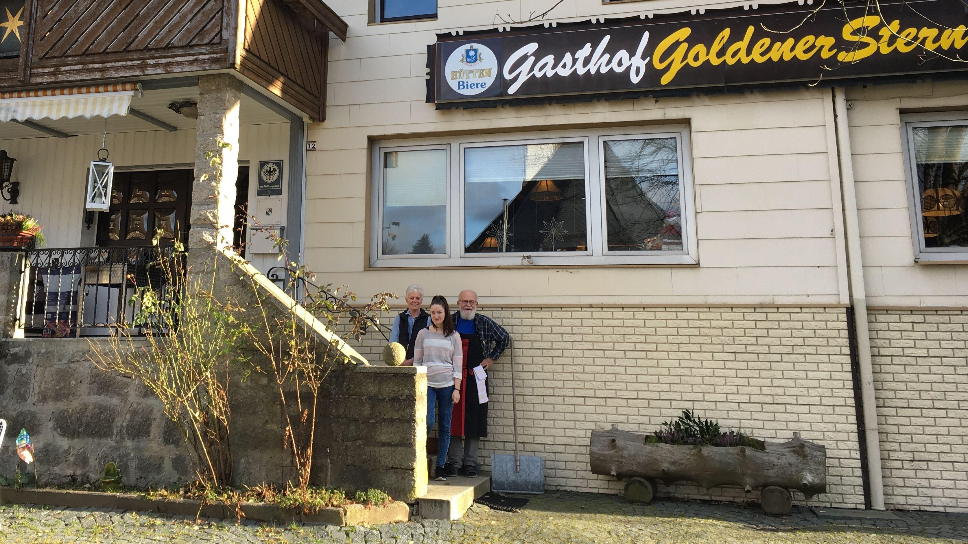 """Drei Personen stehen auf einer Treppe vor dem Gasthof """"Goldener Stern"""" in Oberwarmensteinach im Fichtelgebirge."""