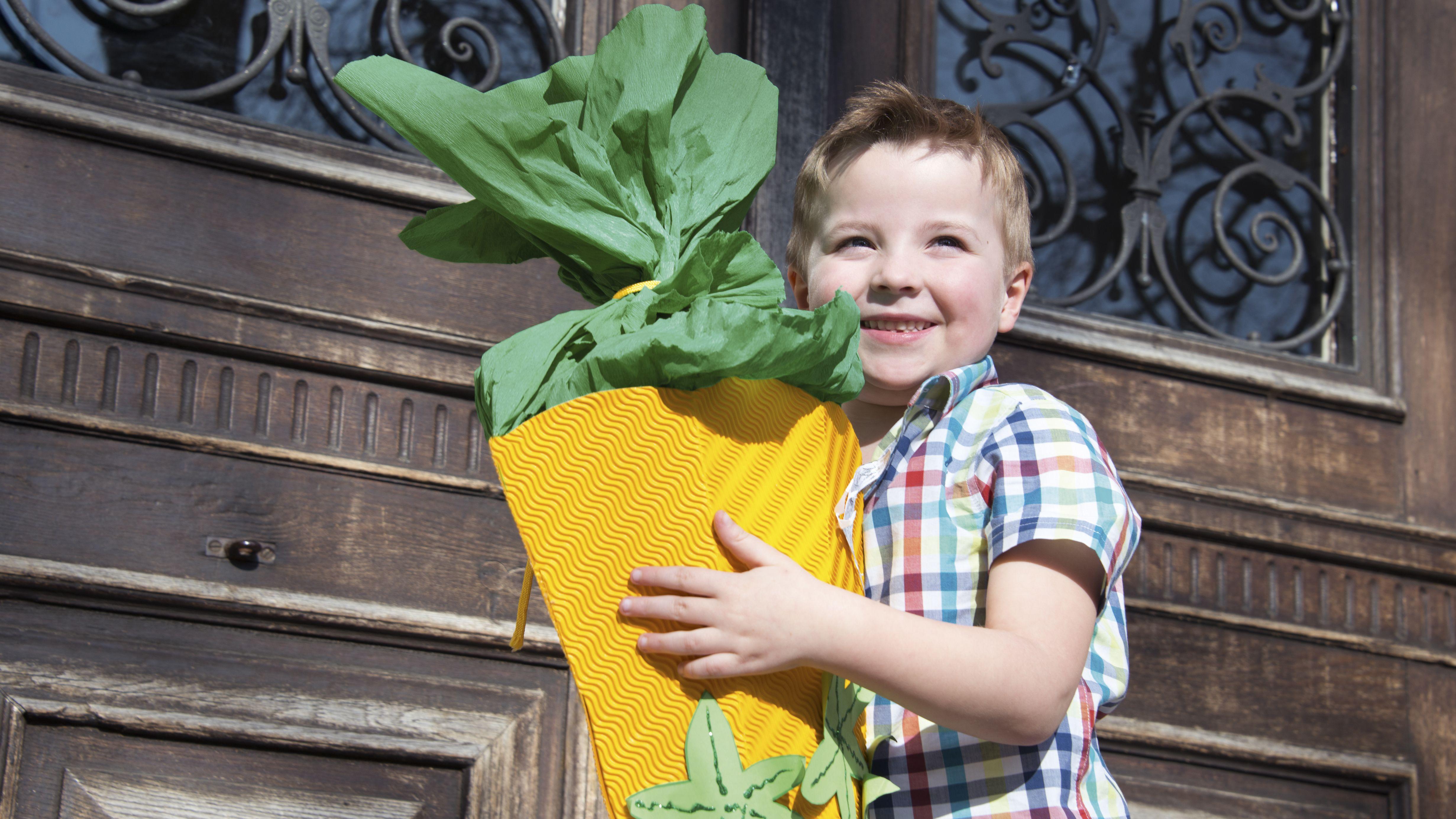 Bub mit Schultüte vorm Eingang einer Schule (Symbolbild)