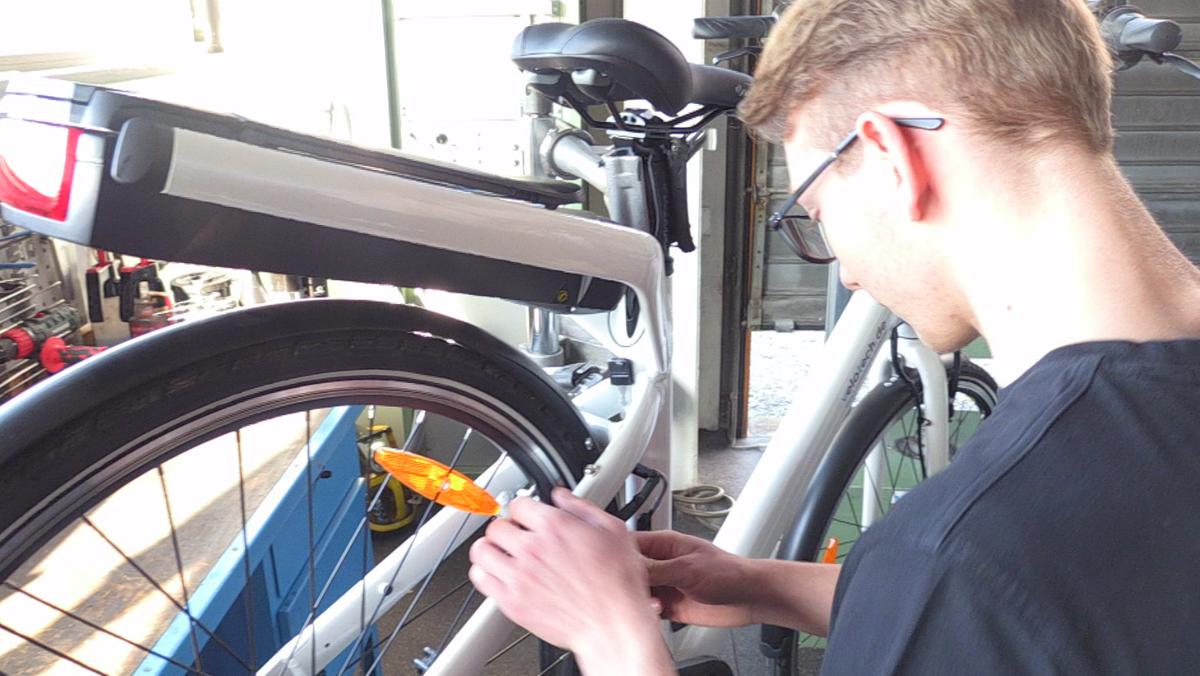 Ein Zweiradmechatroniker-Azubi stellt an einem Fahrrad die Bremsen ein.