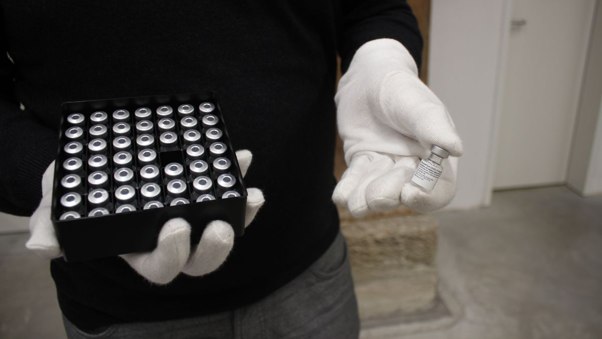 Ein Mensch hält eine Schachtel mit Impfdosen in der einen, eine einzelne Impfdose in der anderen Hand.