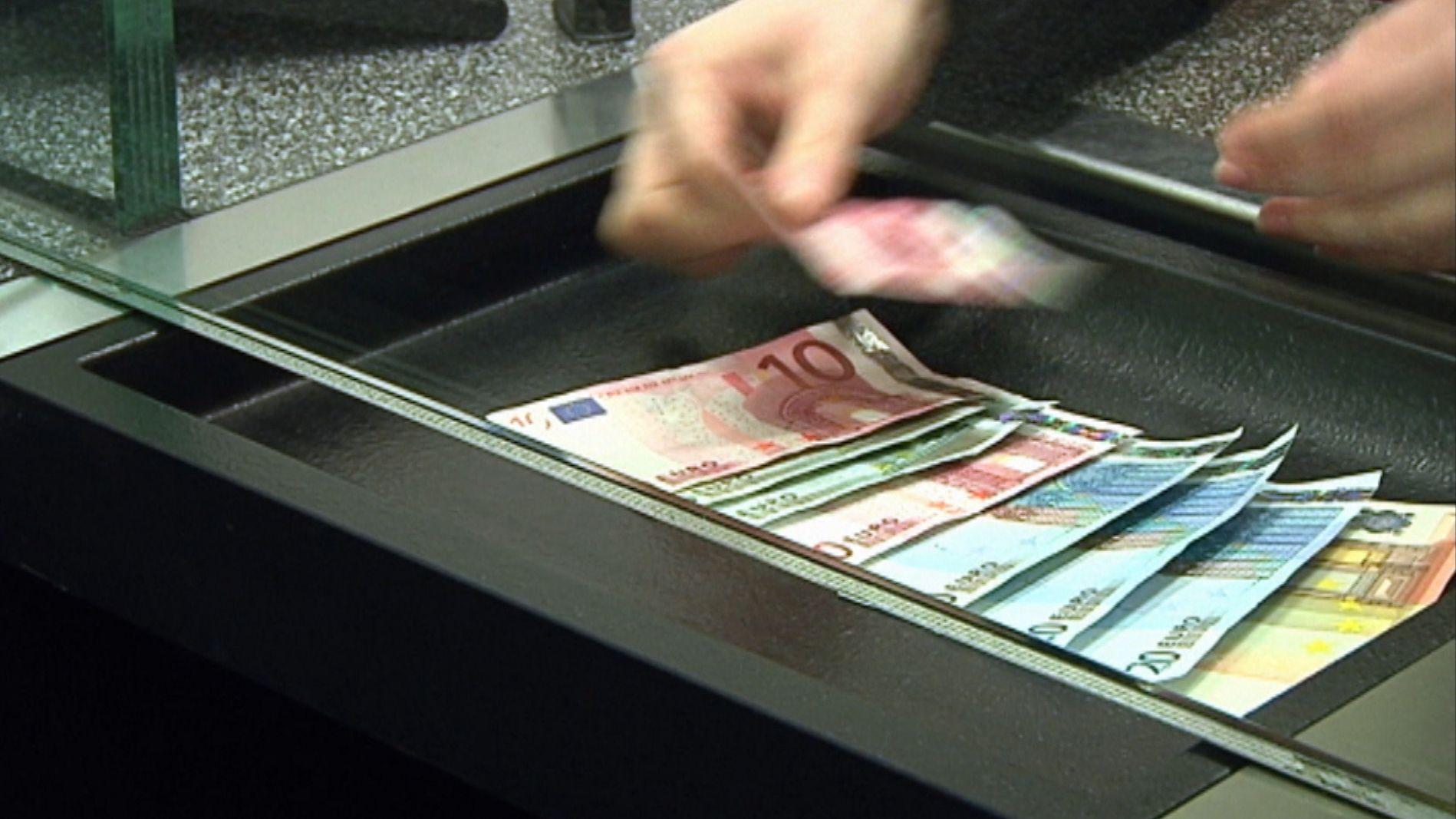 An einem Bankschalter zählt eine Person Geld ab (Symbolbild).